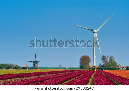 old windmill and new wind turbine in the Netherlands - stock photo