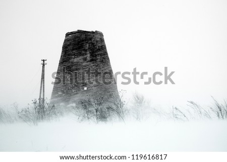 Old windmill at storm - stock photo