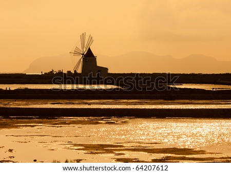 Old windmill at the salt mines at sunset,Sicily,focus on the mill - stock photo