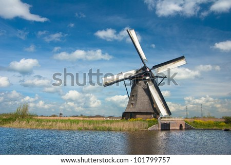 Old windmill in a Dutch countryside with blue sky - stock photo