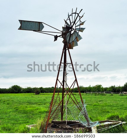 old windmill water tower in a field - stock photo