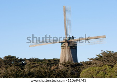 old windmill with blue sky and trees - stock photo