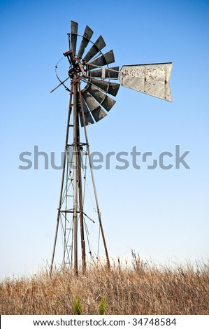 Old windmill, worn out from years of hard work. - stock photo