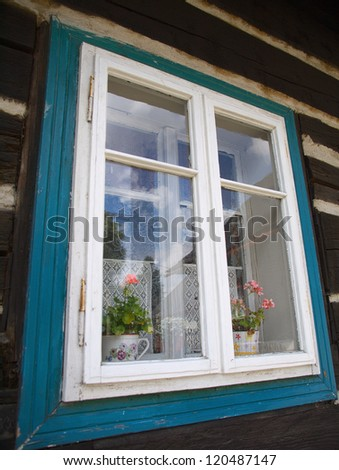 Old window in wooden house - stock photo