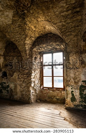 Old window of an abandoned house. Inside the old castle - stock photo