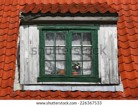 Old window of attic. Window with wooden frame on a tile roof. - stock photo