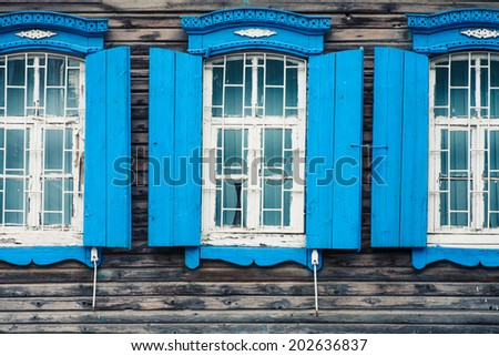 Old window. The window of the old wooden log house on the background of wooden walls. Window of a old wooden cottage - stock photo