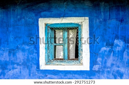 Old window with cyan wooden frame  and crocheted curtain on a blue plastered hand painted wall. - stock photo