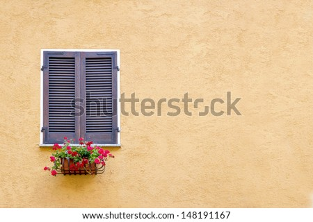 Old window with wooden shutters on yellow stucco wall and copy space - stock photo