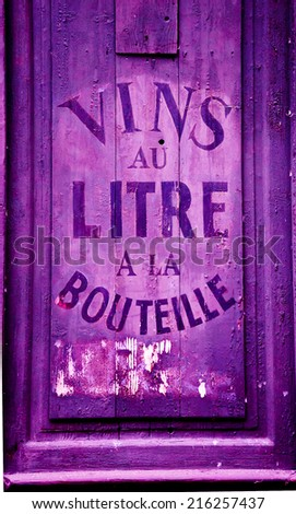 "Old wine and spirit cellar sign. Text in French ""Vins au litre, a la bouteille"" meaning ""Wine selling by liters or in bottles"". Toned photo. - stock photo"