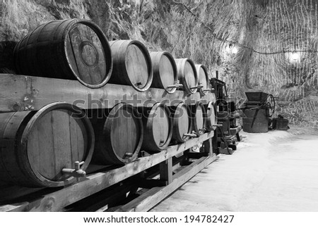 Old wine barrels in salt mine. Black and white image. - stock photo