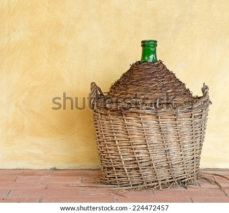 Old wine demijohn carboy, by house. Yellow wall. - stock photo