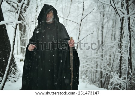 Old wizard in snowy forest . Fantasy and fairy tale - stock photo