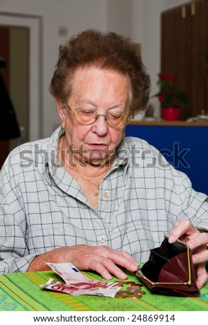 Old woman counts her money - stock photo