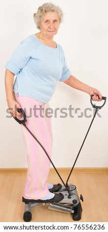 old woman do morning exercise on trainer - stock photo