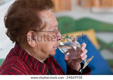 Old woman drinking water from a glass - stock photo
