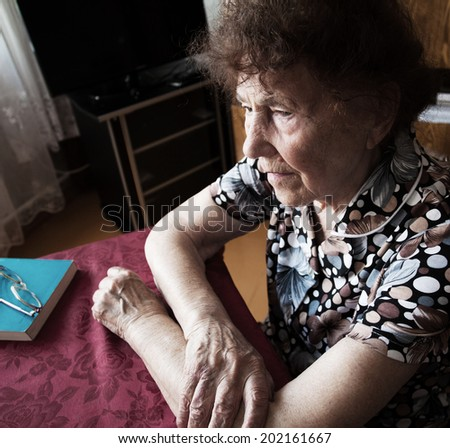 Old woman. Elderly female at home - stock photo