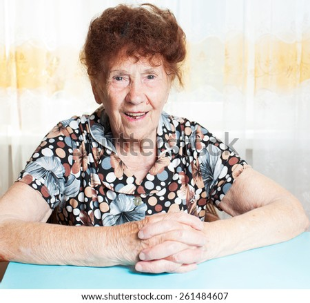 Old woman. Elderly smiling female at home - stock photo