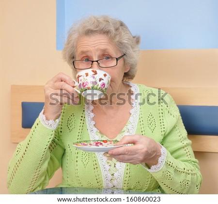 Old woman enjoying coffee or tea cup - stock photo