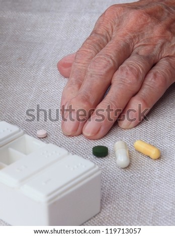 Old woman hand and pills - stock photo