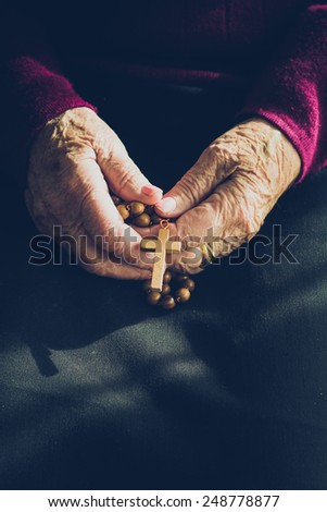Old woman hands in prayer with a rosary - stock photo