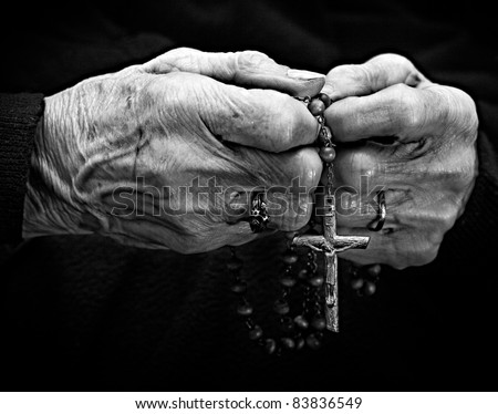 Old woman hands with a rosary - stock photo