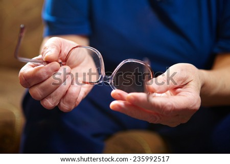 Old woman hands with eyeglasses. Senior people health care. - stock photo