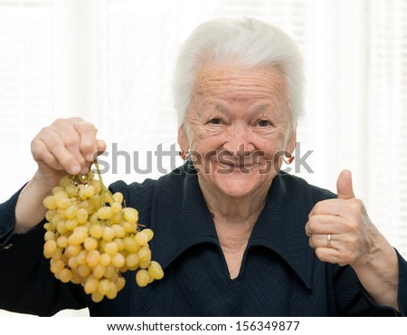 Old woman holding a bunch of grape - stock photo