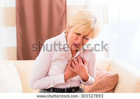 Old woman holding breast because of heart infarction  - stock photo