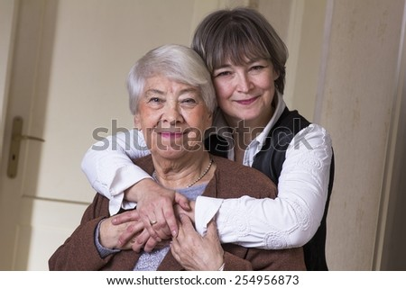 Old woman hugged by daughter. - stock photo
