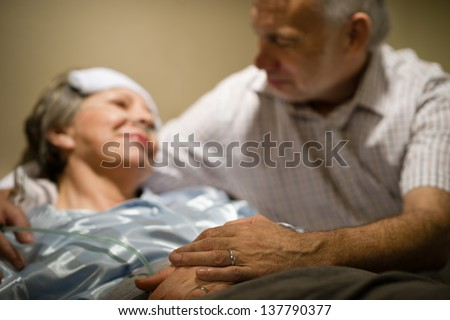 Old woman in pain lying bed holding hands with husband - stock photo
