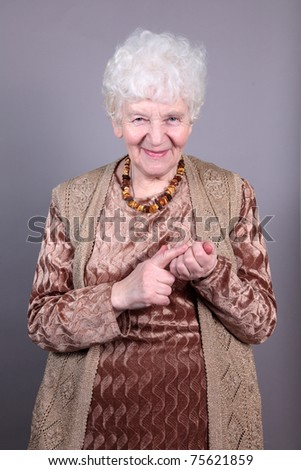 Old woman isolated against grey background - stock photo