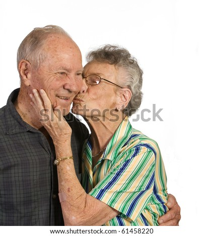 old woman kissing husband. Shot against white background. - stock photo