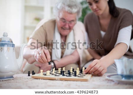 Old woman learning young woman to play chess - stock photo