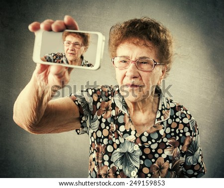 Old woman photographed yourself on the mobile phone. Fan granny makes selfie  - stock photo