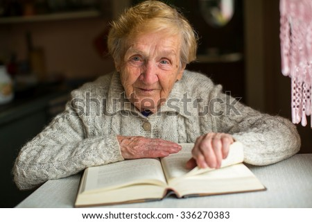 Old woman reading a book sitting at the table. - stock photo