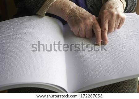 Old woman' s hands, reading a book with braille language - stock photo