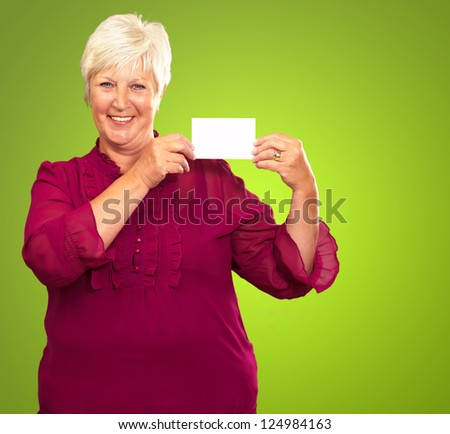 Old Woman Showing  Paper On Green Background - stock photo