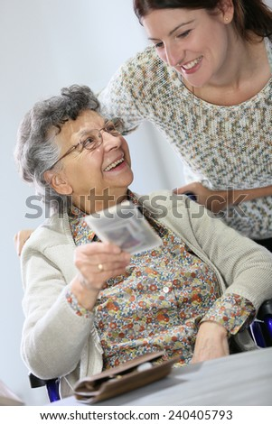 Old woman showing picture to home carer - stock photo