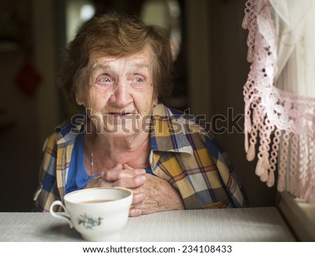 Old woman sitting alone near the window in his house.  - stock photo