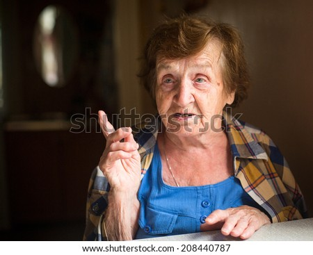 Old woman sitting at table and talk in his house. - stock photo