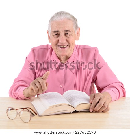 old woman sitting near table with book. makes instructive gesture. portrait isolated on white background - stock photo