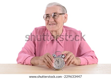 old woman sitting near table with clock. portrait isolated on white background - stock photo