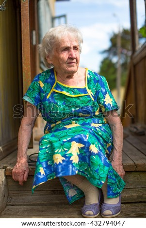 Old woman sitting on the porch of rural house. - stock photo