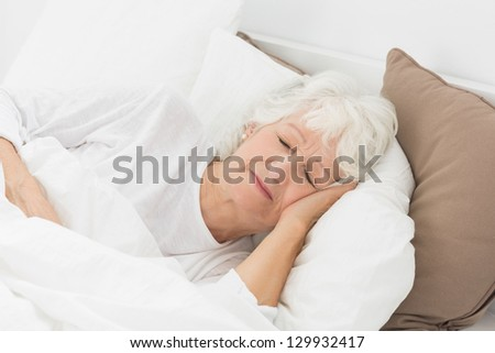 Old woman sleeping on the bed - stock photo
