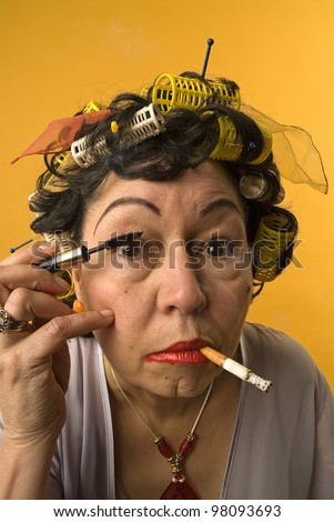 Old woman smoking and applying make up - stock photo