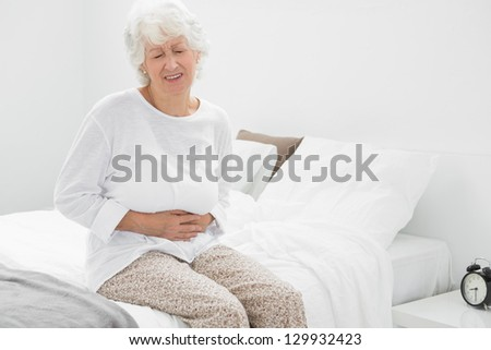 Old woman suffering with belly pain in the bedroom - stock photo
