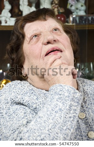 Old woman thinking ,holding her hand to chin and looking up - stock photo
