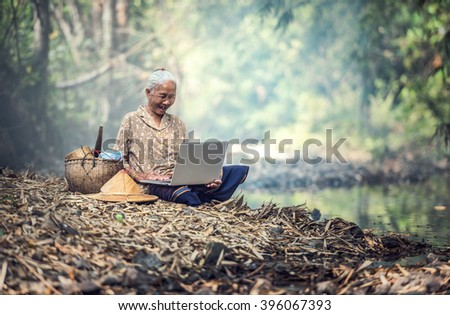 Old woman using a laptop outdoor - stock photo