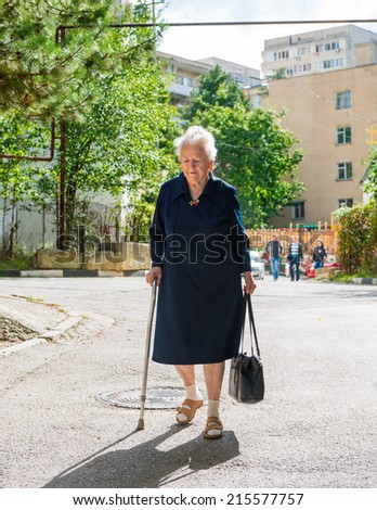 Old woman walking with a cane down the street of the city - stock photo